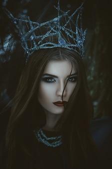 Bela modelo está posando em uma floresta com tecido azul
