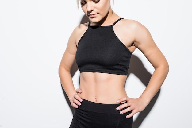 Bela modelo feminina esguia em roupas pretas posando sobre branco