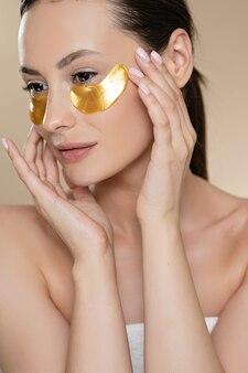 Bela modelo feminino com pele saudável fresca, posando no estúdio com manchas de beleza sob os olhos. mulher caucasiana, usando cosméticos profissionais para reduzir as rugas faciais.