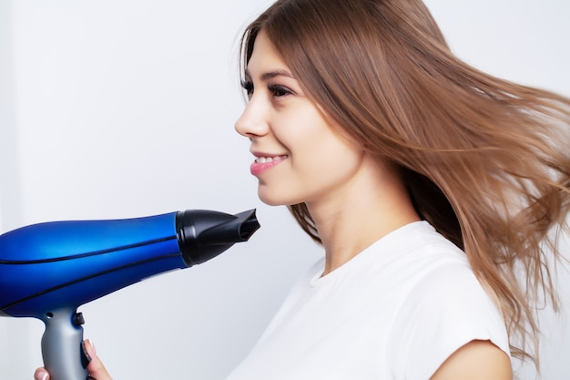 Bela modelo feminino jovem cuida do cabelo dela, usa um secador de cabelo para secar o cabelo