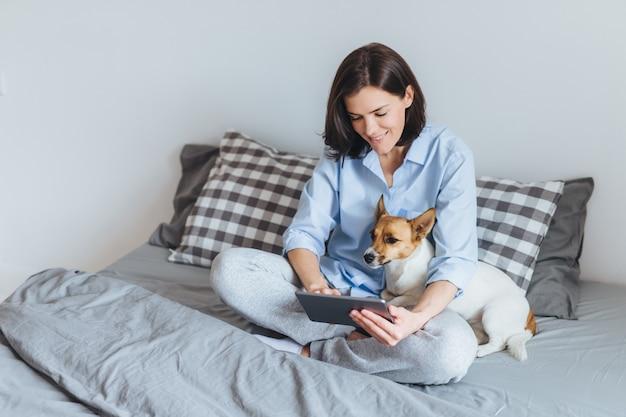 Bela modelo feminino usa pijama, senta-se na roupa de cama no quarto com seu animal de estimação favorito