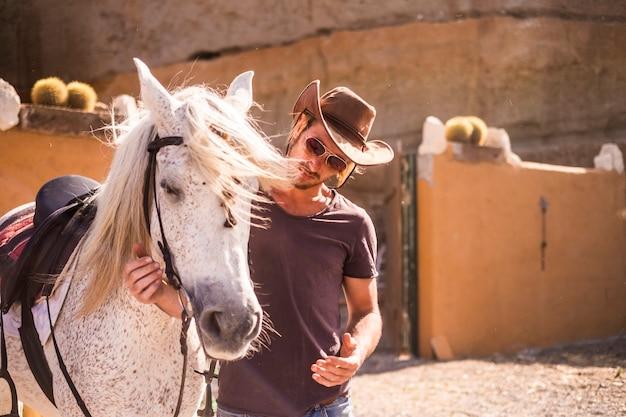 Bela modelo homem loira jovem com cavalo branco na zona rural. melhores amigos para sempre prontos para viver aventuras no campo juntos. amor e terapia de estimação para o conceito de amizade