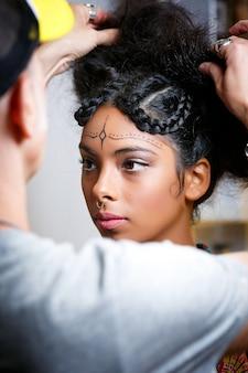 Bela modelo latino-americana com a assistência de uma estilista se preparando para uma sessão de fotos
