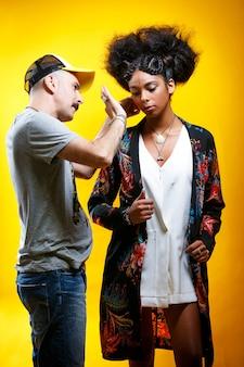Bela modelo latino-americana com a assistência de uma estilista