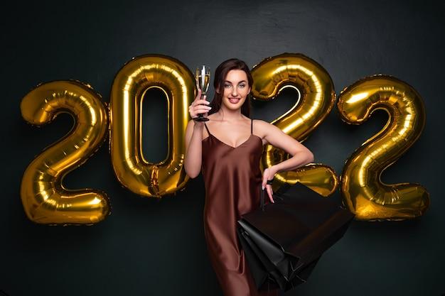 Bela modelo moreno fica em um fundo escuro com letras de balões de ar e segura um copo de c.