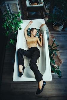 Bela modelo posando em um banheiro com maquiagem prateada criativa