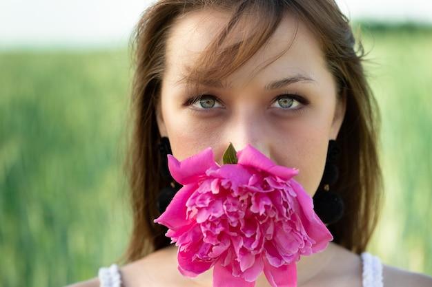 Bela modelo segurando uma flor de peônia rosa na boca em um campo de trigo verde