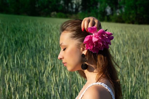 Bela modelo segurando uma flor de peônia rosa no cabelo em um campo de trigo verde
