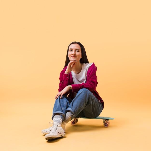 Bela modelo sentado no skate Foto Premium