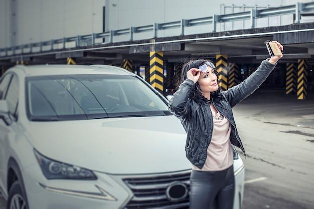 Bela modelo sexy feminina com um carro branco e um smartphone fazendo selfies no estacionamento