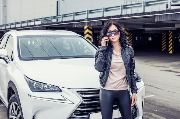 Bela modelo sexy feminina em roupas de couro com um carro branco e um smartphone no estacionamento