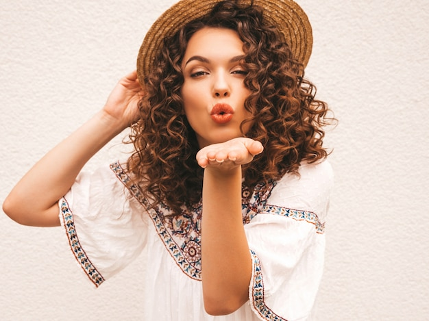 Bela modelo sorridente com afro cachos penteado vestido com vestido branco hipster de verão.