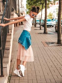 Bela modelo sorridente com penteado de chifres, vestido com roupas de jeans de jaqueta hipster de verão. garota despreocupada sexy, posando na rua. mulher na moda engraçada e positiva, se divertindo em óculos de sol