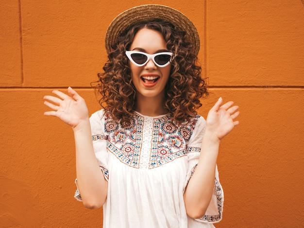 Bela modelo sorridente com penteados de cachos afro, vestida com óculos de sol e vestido branco hipster de verão