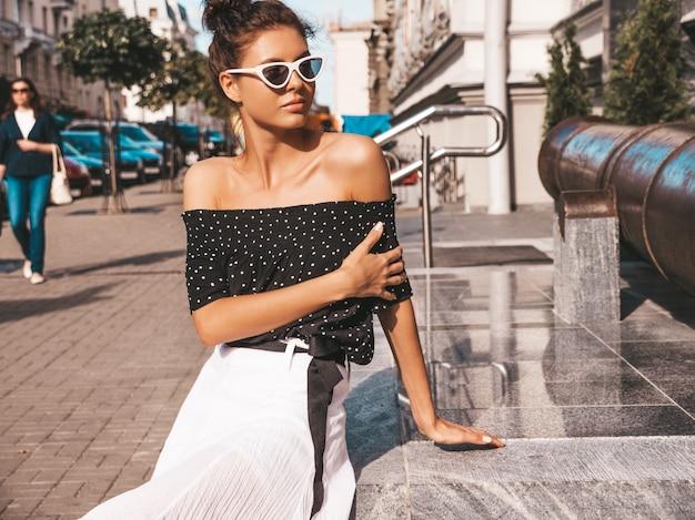 Bela modelo sorridente, vestida com roupas de verão elegante. garota despreocupada sexy sentada na rua. empresária moderna na moda em óculos de sol se divertindo