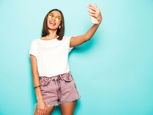 Bela modelo sorridente, vestida com roupas de verão hipster. garota despreocupada sexy, posando no estúdio perto da parede azul em shorts jeans. mulher na moda e engraçada, tirando fotos de auto-retrato de selfie no smartphone