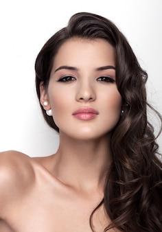 Bela modelo usando acessórios de casamento de cabelo com pérolas para noiva linda na parede branca