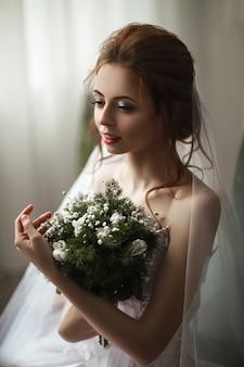 Bela modelo usando vestido de renda branca está posando