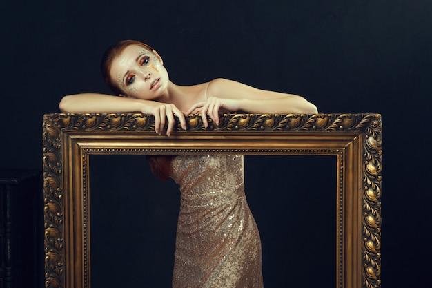 Bela modelo usando vestido dourado está posando