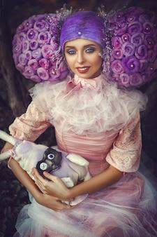 Bela modelo usando vestido rosa posando com uma peruca roxa