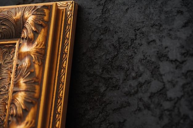 Bela moldura dourada na parede preta com padrão close-up