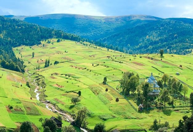 Bela montanha de verão e uma pequena aldeia na encosta da montanha (cárpatos. ucrânia)