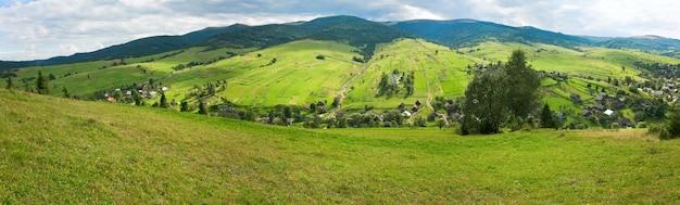 Bela montanha de verão e vila na encosta da montanha (cárpatos, ucrânia). três tiros costuram a imagem.