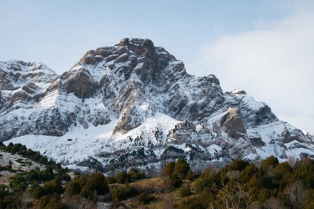Bela montanha rochosa coberta de neve sob um céu nublado