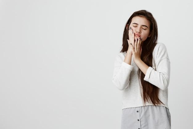 Bela morena adolescente mulher vestindo seus longos cabelos escuros e lisos soltos em roupas casuais, tocando as bochechas com as mãos, posando contra parede cinza com os olhos fechados.
