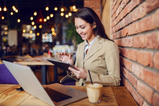 Bela morena caucasiana vestido inteligente casual sentado no café e usando o tablet. na mesa estão laptop e café.