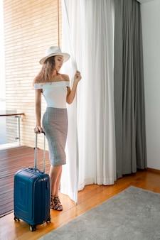 Bela morena com cabelos cacheados em um chapéu claro, uma blusa branca e uma saia longa de salto alto posa em pé em um quarto com uma mala azul nas mãos