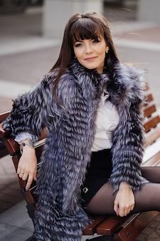 Bela morena com cabelos longos e lisos, vestindo um casaco de pele cinza, camisa branca e saia preta no banco e sorri pensativamente
