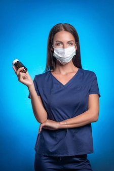 Bela morena com o cabelo dela posando em pé contra um fundo azul em uma máscara protetora na frente, segurando um frasco de medicamentos na mão. enfermeira. cuidados de saúde. foto vertical.