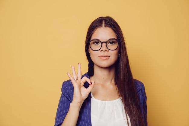 Bela morena de óculos com cabelos longos, vestido de terno azul escuro, mostra sinal ok, parece confiante, sobre fundo amarelo, com espaço de cópia. conceito de pessoas bem sucedidas.