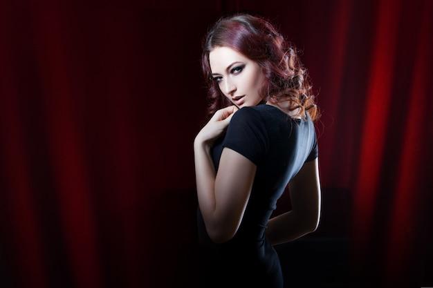 Bela morena de vestido preto na cortina vermelha