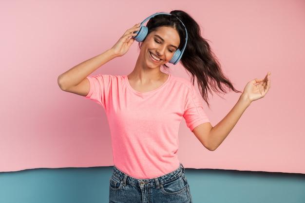 Bela morena em fones de ouvido ouve música.