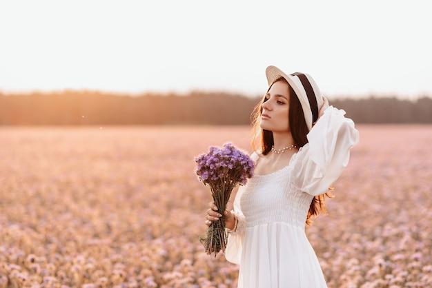 Bela morena em um campo de lavanda ao pôr do sol. retrato incrível