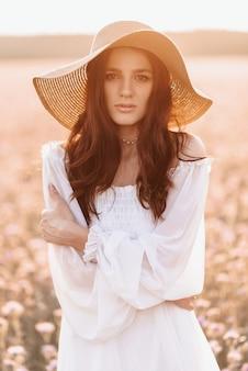 Bela morena em um campo de lavanda ao pôr do sol.