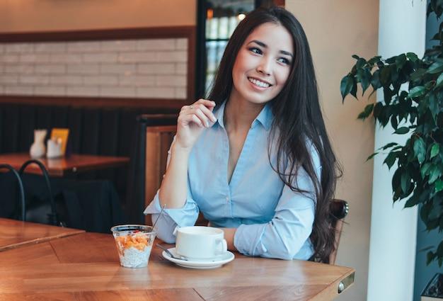 Bela morena encantadora sorridente menina asiática tem café da manhã com café e pudim de chia no café