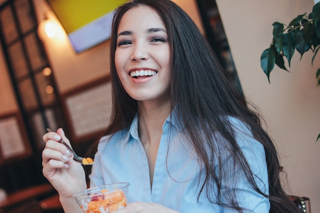 Bela morena encantadora sorridente menina asiática tem café da manhã com pudim de chia no café