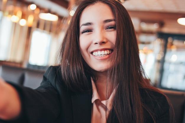 Bela morena encantadora sorridente menina asiática tomando selfie na câmera frontal no café