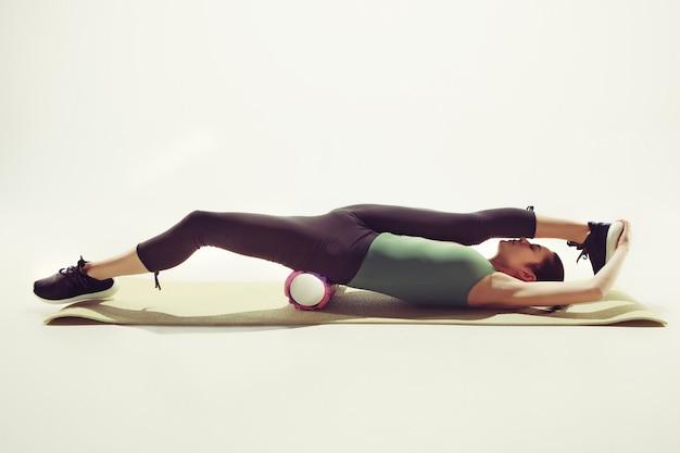Bela morena esguia fazendo exercícios de alongamento em uma academia