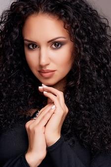 Bela morena jovem com cabelos cacheados e maquiagem brilhante