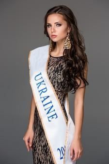 Bela morena jovem com o cabelo dela posando em um vestido traceria.