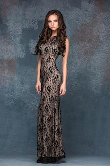 Bela morena jovem com o cabelo dela posando em vestido longo ai.