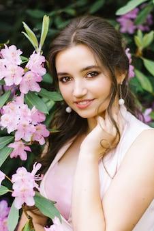 Bela morena jovem, com um sorriso e grandes olhos castanhos em jardins florescendo de rododendros rosa