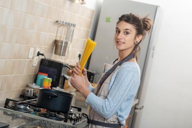Bela morena jovem cozinhando na cozinha
