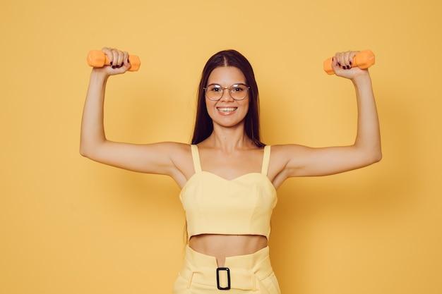 Bela morena jovem de óculos, vestido com blusa e calça amarela, sorrindo largo, halteres levantados mostra seu bíceps feliz em exercitar e ser saudável. conceito de pessoas confiantes.