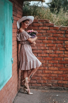 Bela morena jovem em begie dot vestido posando ao ar livre perto da parede de tijolo vermelho