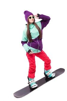 Bela morena jovem em traje de esqui roxo monta snowboard preto